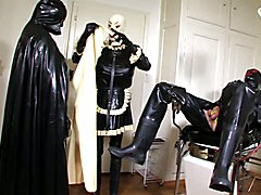 Latex cape mistress Karin plays with latex maid Leila and a latex cock toy. The cock toy is ...