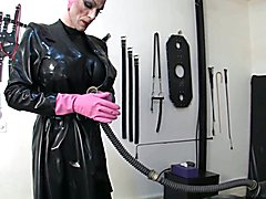 latex mistress leila plays with her latex toy. Leila wears a black latex catsuit with big ti...