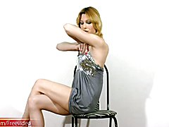 Blond shemale poses in her short silver dress showing off her long bare legs. She does a kin...