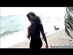 Teen ladyboy girlfriend flashes her tits at the beach and masturbates her big cock on the st...