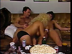 Tall tranny in blonde wig sucks cock while getting fucked in threesome
