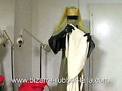Rubber nurse Leila bounds the rubber cock doll now with some rubber aprons, puts her a disci...