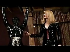 Strict Transsexual Mistress dominates her horny, latex encased gimp.