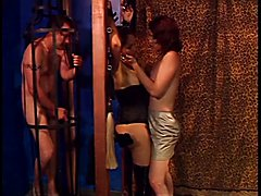 Caged slave jacks off while a she-male mistress takes care of another she-male slave