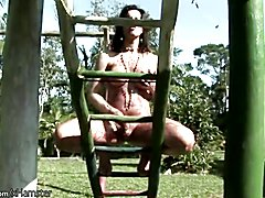 Naked t-girl swinging in the park gets covered in chocolate