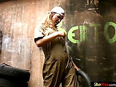 This lovely t-girl is hard at work in the garage fixing tires dressed in her overalls and ha...