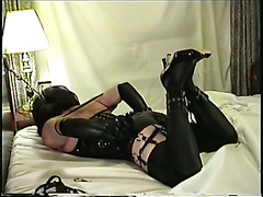 a continuation of Miss Christi bound in rubber on chair.  This time she is tied to the bed a...